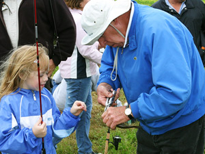 Friends volunteer assisting a young angler at the Youth Fishing Fun Day